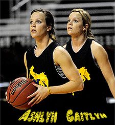 Image of the Baggett Twins of McNeese State Cowgirls basketball team in yellow on black uniforms picturing a cowboy on a bucking bronco, Ashlyn, on left with ball, Caitlyn on right.