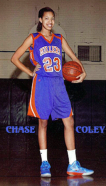 Image from 2013 of Chase Coley, girls high school basketball player for the Wasburn Millers, standing, with a basketball on her hip, in her number 23 Millers uniform.