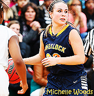 Michelle Woods, Wheelock College basketball player, dribbling ball, in gold on blue uniform, number 12.