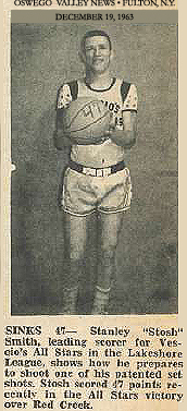 Uncredited image from the Oswego Valley News, Fulton, N.Y., December 19, 1963, showing Stanley (Stosh) Smith, Vescio's All-Stars basketball team player, posing with basketball with the number 47 on it. Text reads: SINKS 47-- Stanley 'Stosh' Smith, leading scorer for Vescio's All Stars in the Lakeshore League, shows how he prepares to shoot one of his patented set shots. Stosh scored 47 points recently in the All Stars victory over Red Creek.