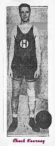 Image of basketball player, Chuck Kearmey, shwn facing camera with basketball on floor in uniform with large H in white circle on jersey, for the Hollywood Athletic Club team. From The Los Angeles Times, L.A., Caifornia, February 8, 1925.