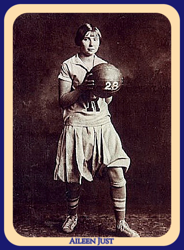 Image of Minnesota girls basketball player on the Rapidan High School team (1928), posing in skirt uniform with R on front, striped socks, holding ball (with number 28 on it) with both hands on it out front, looking at camera.