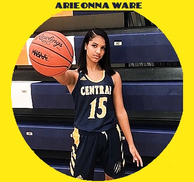 Picture of Arieonna Ware, girls high school player for Central High School in Battle Creek, Michigan. In black uniform with yellow lettering, number 15, in front of folded stands, holding basketball towards us with one arm, her right hand holding the ball.