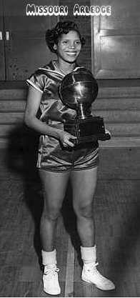 Newspaper photo of Missouri Alredge, Hillside High (Durham, North Carolina) basketball player, holding championship trophy of the Bull City Tournament. From the Washington Afro-American, Washington D.C., Mar. 24, 1953. The caption reads: High-Scoring Champ, and the text reads: Missouri (Pos) Arledge, Hillside high school senior star of Durham, N.C. holds trophy her school won in the recent Bull City cage tourney. She scored 54 of her team's points in defeating Little River, 81-26 and amassed a season's scoring record of 586 points in 19 games with a 31.3 point per game average.