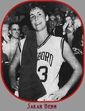 Black and white image of Sarah Behn, Foxboro High School (Massachusetts) girls basketball player, on sidelines, towel on shoulder, hands on hips, head cocked and smiling. From The Boston Globe, March 7, 1989..