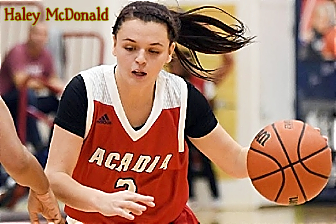 Image of Haley McDonald, Acadia University Axewoman, women's basketball player in Canada. In action shot in red uniform with white at top and black short sleeves, with basketball, dribbling.