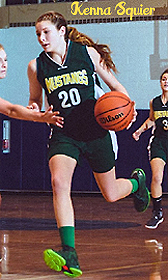 Image of girls basketball player, Kenna Squire, of the Sussex County Technical School Mustangs in New Jersey, taking the ball upcourt in her black uniform with gold lettering, number 20.