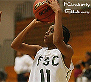 Kimberly Blakney shooting the ball to our left, with both hands, in photo, with ball above her head.