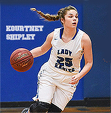 Image of Kourtney Shipley, Bradleyville (Missori) High School girls' basketball player, dribbling basketball with pigtail flying back to the left, in white uniform with blue lettering, LADY EAGLES, number 25.