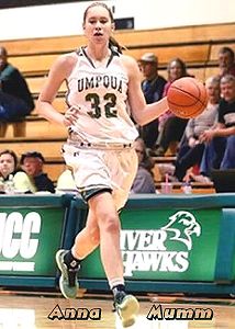 Anna Mumm, Umpqua College women's basketball player, number 32, coming up court with basketball.