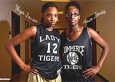 Image from 2014-15 season, posing in dark green uniform tops ina dorm hall. Mya on left, Asia on right. Side by side, with hands on hips, Mya, LADY TIGERS, in white, surrounding number 12; Asia unumbered, COMMERCE TIGERS surrounding a basketball, all in white.