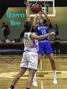 Destiny Castro shooting a basketball, being defended, in a blue ROYALS 310 uniform. Ohoto by Mark Scott/Pacific Daily News.