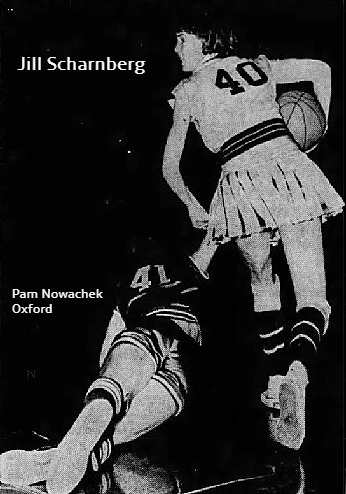 Image from the Iowa State Girls' Basketball Tournament in Des Moines, 3/11/1964, Everly High winning 78 to 68 over Oxford High. Pictured is Jill Scharnberg, Everly, number 40, in  white uniform with pleated skirt, back to us, but face in profile, looking to our left, sprawling on the ground, also with back to us, having dove for the ball, is #41, Pam Nowachek, of Oxford, in dark uniform. Picture from the Des Moines Tribune, March 12, 1964, photo by Jack Brinton.
