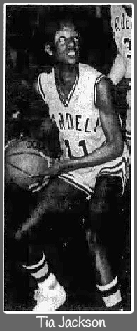 Image of Tia Jackson, sophomore girls basketball player for Mardela Springs High, crouched and about to shoot the ball, in white MARDELA #11 uniform. From The Daily Times, Salisbury, Maryland, February 20, 1988.