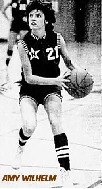 Picture of Iowa girls basketball player, Amy Wilhelm, North High School (Sioux City). with a basketball looking to her right, to our left, in a white on black uniform, #21, with a black N inside a white star on her right side, white and black stripes on the sleeves and collar, stroped socks. From the Sioux City Journal, Sioux City, Iowa, Dec. 23, 1982.