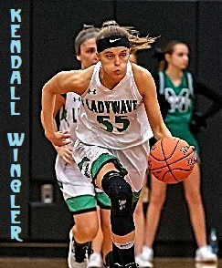 Image of girls basketball player, Kendall Wingler, Meade County High School (Kentucky) dribbling the ball towards us, with puffed cheeks, in white LADYWAVE uniform with green lettering, number 55.