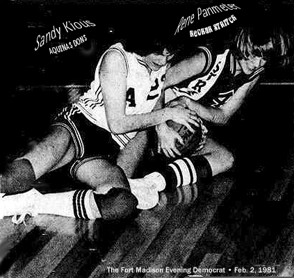 Image from the Fort Madison Evening Democrat from February 2, 1981. Sandy Kious of the Aquilas high school Dons and Rene Panmeter of Keokuk Stritch fight for the ball on the floor during a 2/1/1981 game. Final score saw Aquinas win, 57-52.