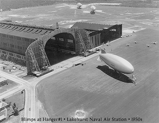 Photo from 1950s of large blimp, possibly the over 400 foot long Vigilance (ZPG-3W), the largest blimp in history, outside historic Hanger One, at Naval Air Station Lakehurst, Lakehurst, New Jersey. Hanger 1 once saw the Zeppelin Hindenburg barely fitting inside, and also four rigid airships, including the Shenendoah, the Los Angeles and the Akron. Two additional blimps are also sitting on the tarmac in the distance. Also in this view are the adjoining smaller hangers 2 & 3.