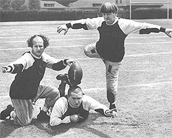Still from the movie, 'Three Little Pigskins' with the Three Stiiges. Image of Larry holding football on top of Curly's head with Moe about to kick the ball. This is probably the first film to credit Lucille Ball for her role.