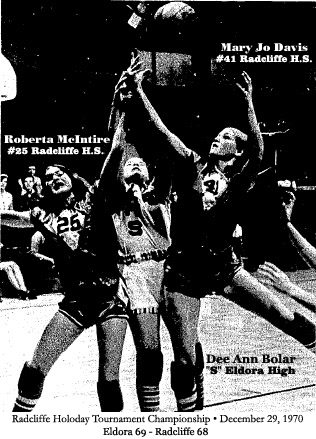 Roberta McIntire (number 25) and Mary Jo Davis (number 41), Radcliffe High School basketball players, are leaping on either side of Eldora High's  Dee Ann Boler (letter S), all trying for the basketball, in a play from the Radcliffe Holiday Tournament Championship game, December 29th, 1970; final score Eldore 69 - Radcliffe 68.